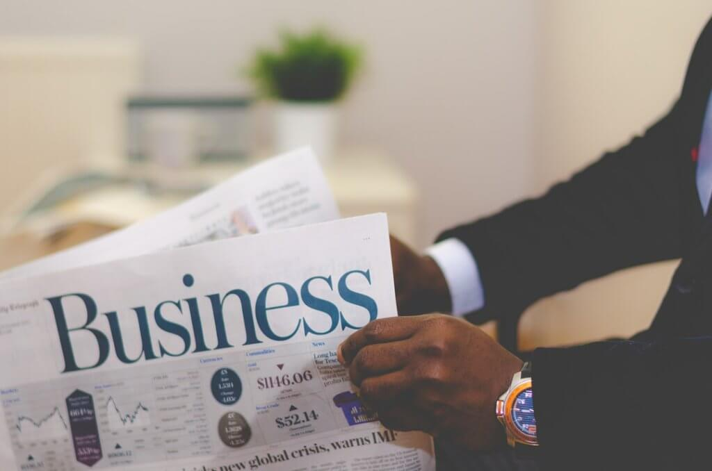 man reading business journal newspaper